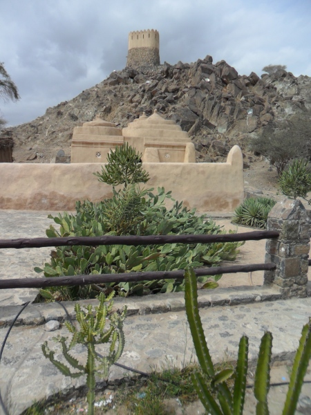 small mosque at the base of a hill with a tower at the top of the hill