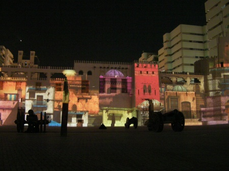 colorful buildings projected on the side of the fort