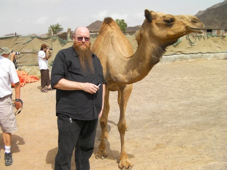 man posing with a camel