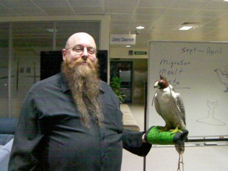 man holding a hooded falcon