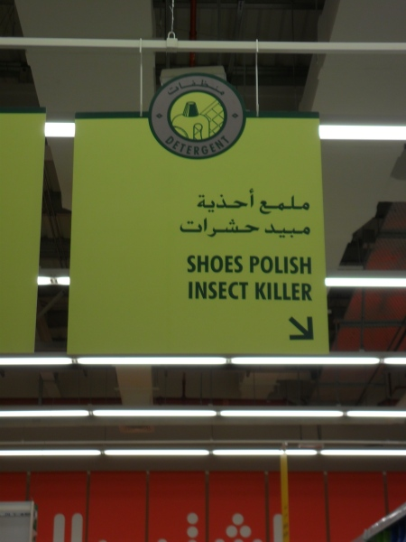 "grocery store aisle sign stating ""shoes polish insect killer"""