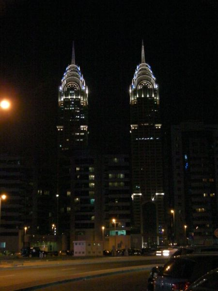 a matching pair of skyscrapers lit at night