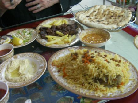 plates of rice, meat, salad, hummos, and bread