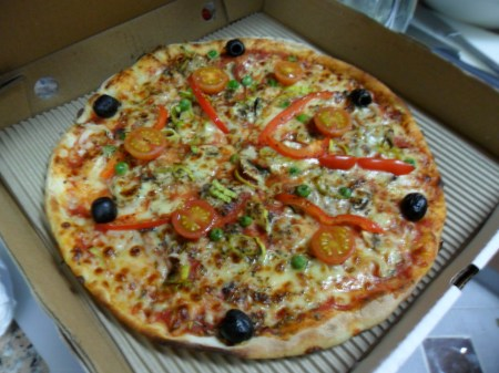 pizza topped with six olives, some tomatoes, green peas