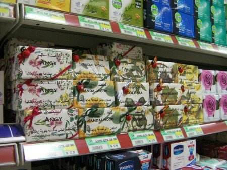 store shelf displaying several flavors of handcrafted soap