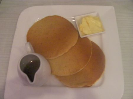 three pancakes, pitcher of syrup and butter