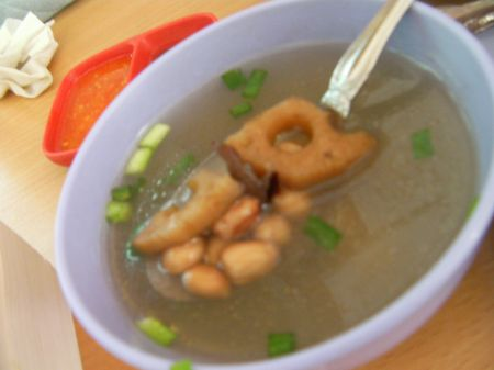 clear broth with green onions, peanuts, lotus root