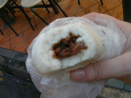 pork bun with bite taken out of it showing the filling