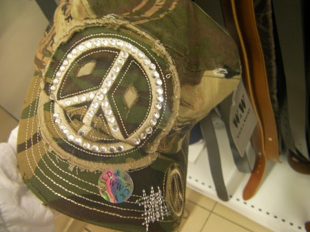 baseball cap made of camouflage material with a large peace symbol made of rhinestones