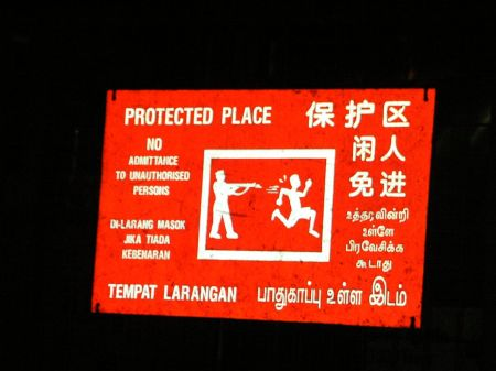 warning sign showing one figure aiming a gun at another figure running away