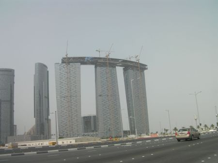 three towers under construction with a connecting structure across the top