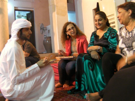 young Emirati man talking with three women