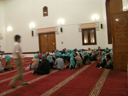 approximately 50 people seated on the floor in the mosque