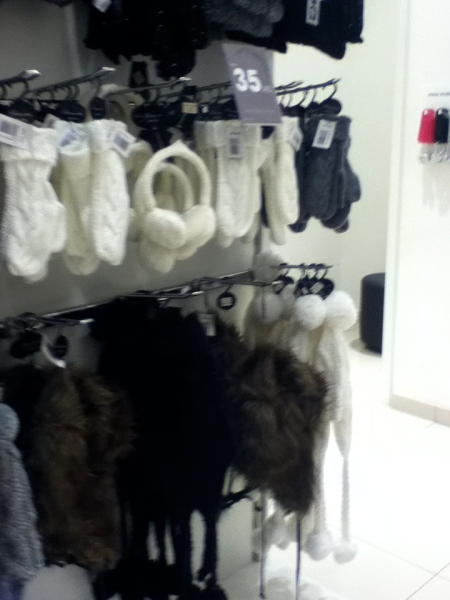 store rack of gloves, ear muffs, and stocking caps