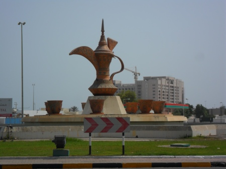 statue of an Arabic coffee pot surrounded by cups