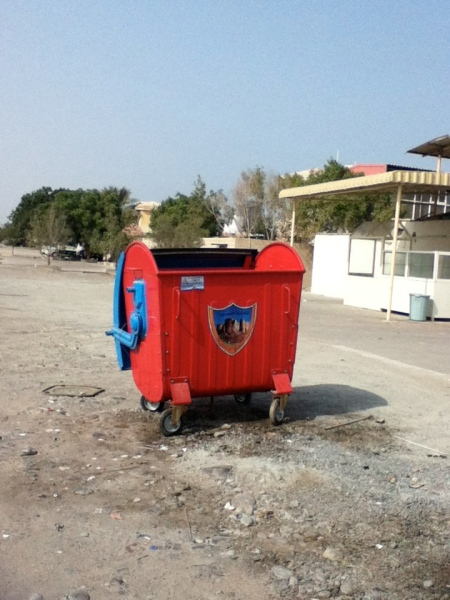 red and blue dumpster with city emblem on the front