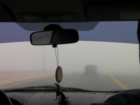 view through the car windshield showing another vehicle a few car lengths ahead which is barely visible