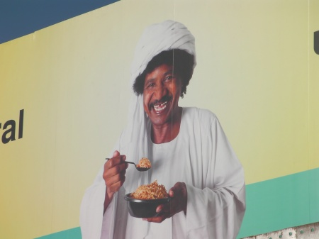 close up of man pictured on the billboard in Middle Eastern clothing and turbin, grinning big as he eats food