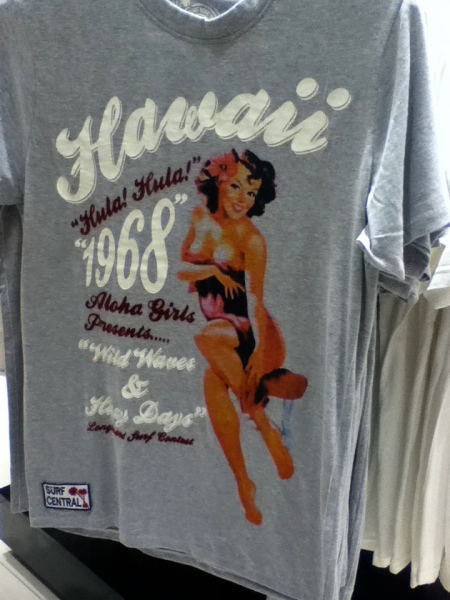 t-shirt with a scantily clad woman and lettering stating Hawaii hula hula 1968 aloha girls presents wild waves and hazy days