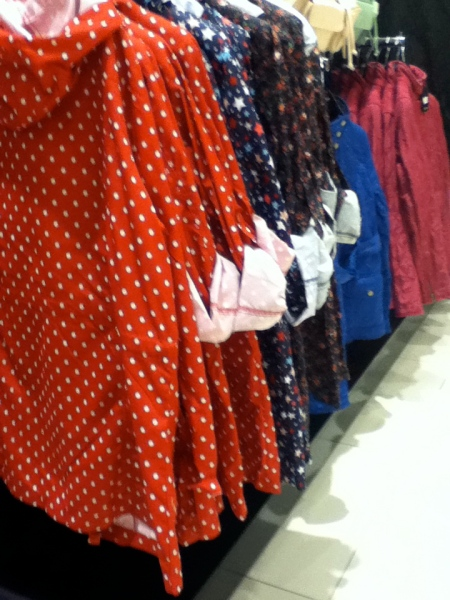 colorful, unlined rain coats on the store rack