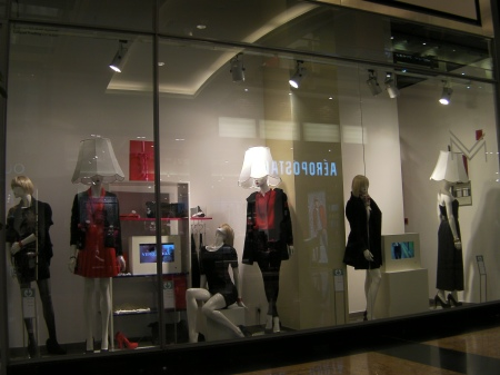 store window with manikins that have lampshades on their heads