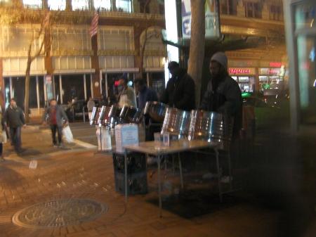 4 men playing steel drums on a street corner