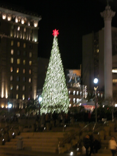 large lighted tree with red star at the top