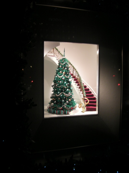 window display with a Christmas tree next to a staircase