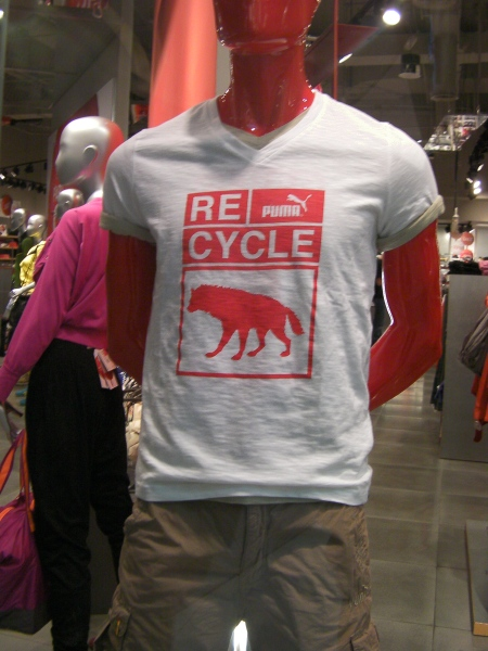 "t-shirt in a shop window, Puma brand, states ""recycle"" and shows the silhouette of a hyena"