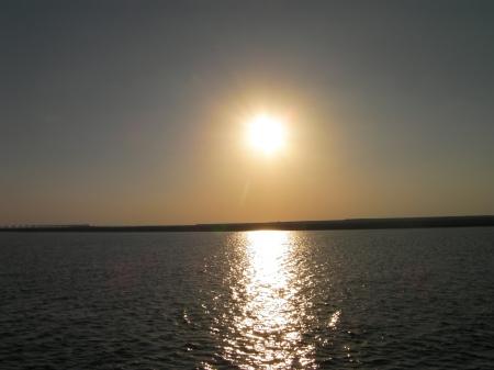 sun approaching the horizon, shining on the water