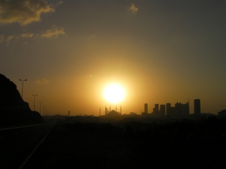 city skyline silhouetted in front of the sun