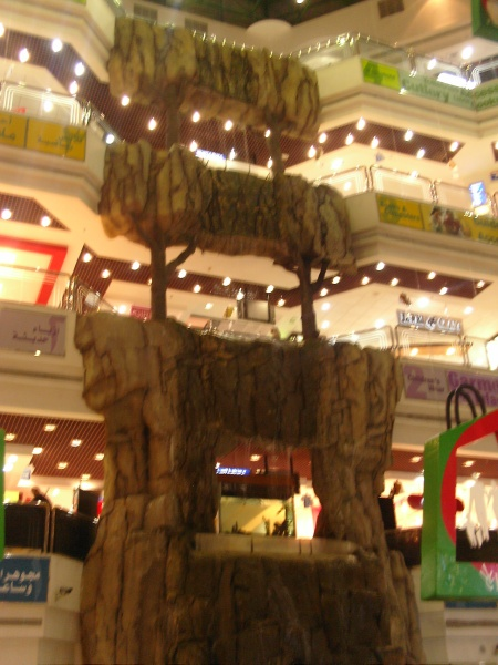 three floors of shopping mall with fake stone waterfall
