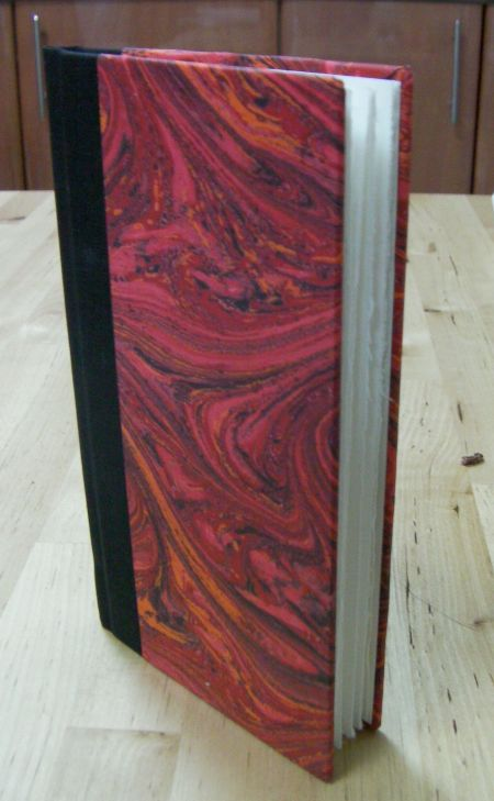 small book with black spine and red cover