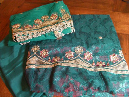 teal fabric with gold and red embroidery in the shape of flowers