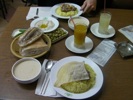 dishes of rice, meat, bread, moutabel, mango juice, lemon juice
