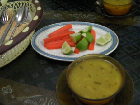 plate of carrots and limes and a bowl of soup