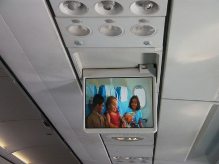 airplane drop down screen showing safety video