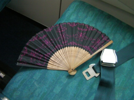 Japanese style fan on an airplane seat