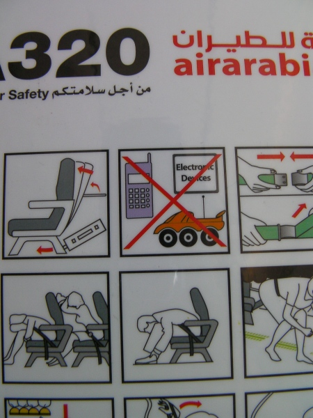 close up of the airplane safety guide sheet showing a red X through a remote control toy car