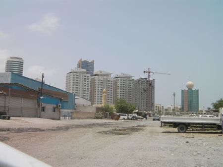 skyscrapers in distance, unpaved road and old industrial shops in foreground