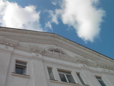 blue sky, white clouds, ornate gable of an old building