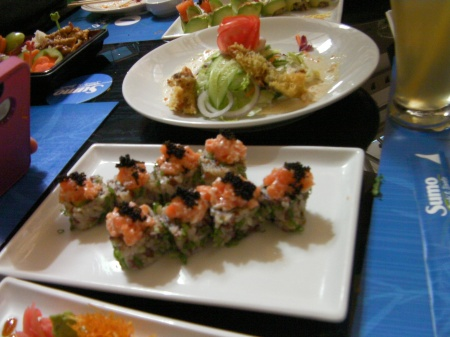 sushi roll of brown rice topped with salmon