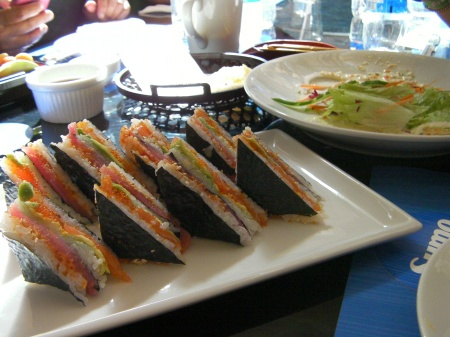 rice, salmon, tuna layered and cut in triangle shapes