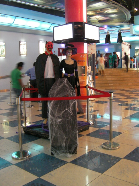 a female mannequin dressed as a witch and a male mannequin dressed as a devil with a coffin