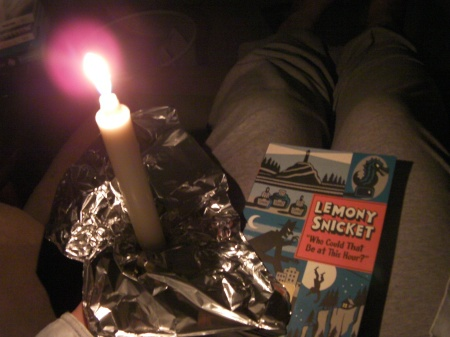 a book, candle, and make-shift aluminum candle holder