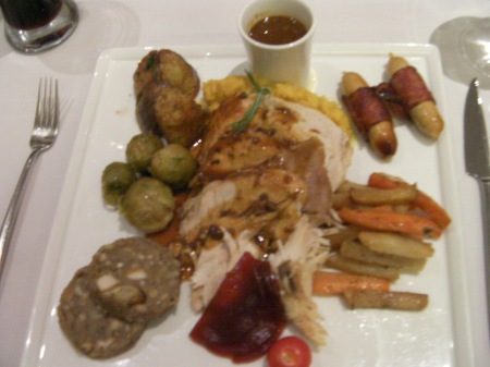 plate of turkey slices, brussel sprouts, carrots, sausages, potatoes, stuffing, cranberry sauce