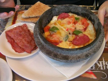 clay pot containing layered bread, fried eggs, tomatoes, bell peppers, pepperoni, cheese