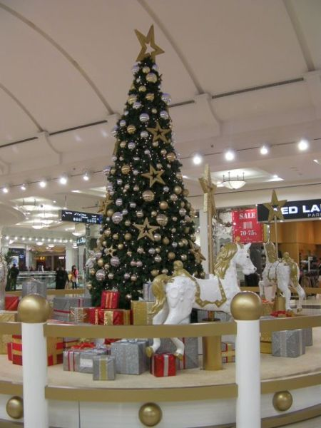 Christmas tree decorated in gold and silver surrounded by carousel horses