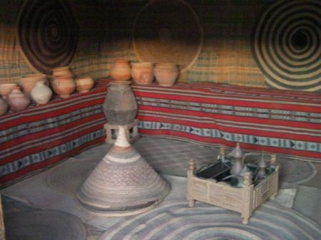 interior of house with coffee pot, clay pots, woven mats