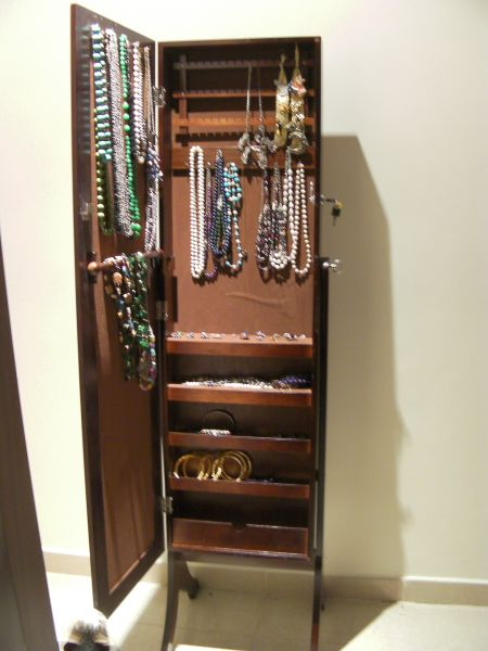 a free standing full length mirror with a  jewelry storage area inside